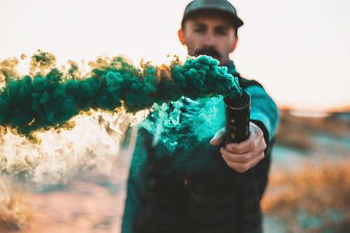 apparel man holding bottle with green smoke clothing