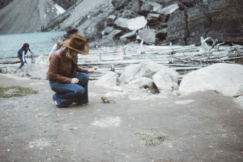 apparel man in brown jacket and blue denim jeans sitting on gray rock during daytime clothing
