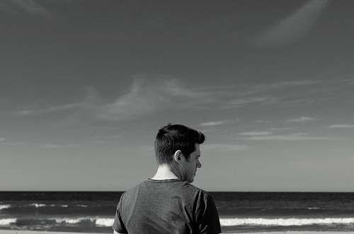 person man near ocean black-and-white