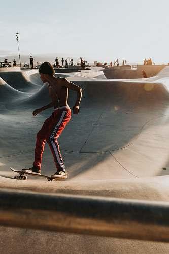person man playing skateboard during daytime people