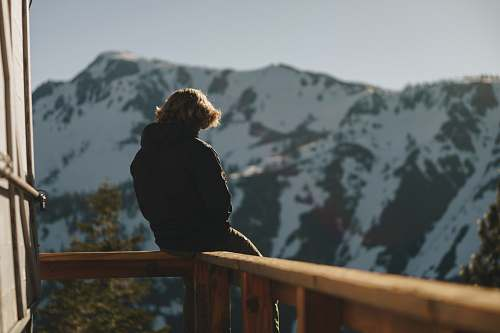 person man sitting on balcony overlooking snow capped mountain people