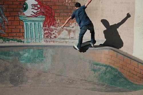 person man skateboarding on concrete rail people