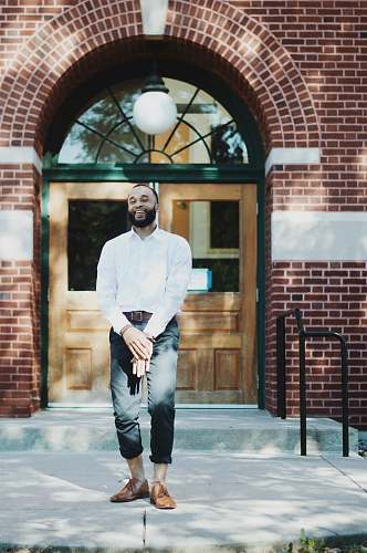 person man standing in front of brown wooden door during daytime people