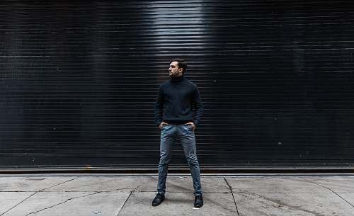 people man standing near black shutter door person