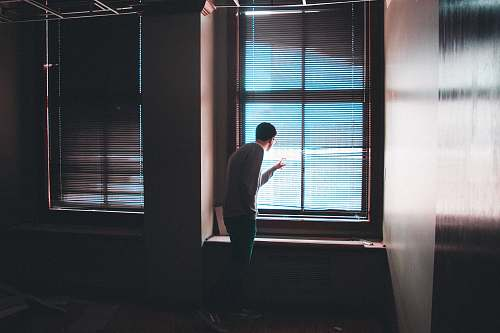 person man standing near window inside building people