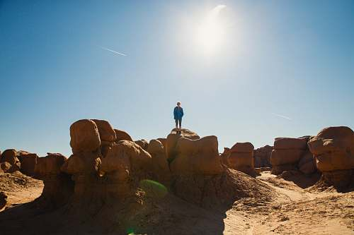 nature man standing on rock formation during daytime outdoors