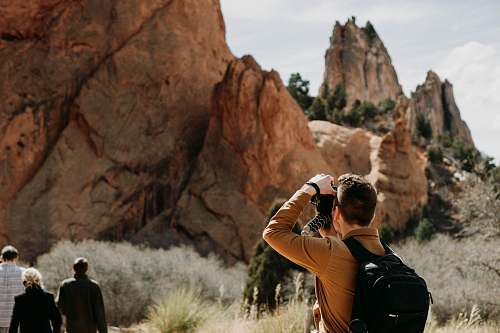 person man taking photo of rock formation people