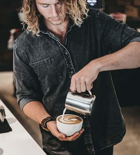 person man wearing black denim jacket pouring white liquid on cup with latte art people