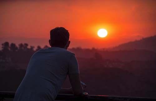 people man wearing blue shirt looking at sunset person