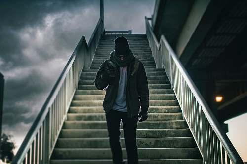 people man wearing brown jacket walking on the stair under black sky person