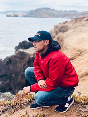 person man wearing cap and jacket squatting on top of the cliff looking the overview people