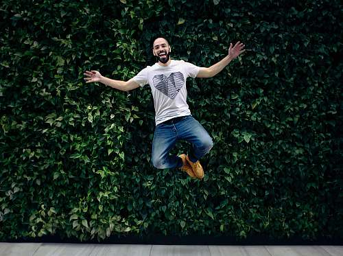 people man wearing t-shirt and jeans jumpshot in front of a green hedge person