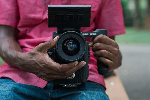 person person holding black DSLR camera camera
