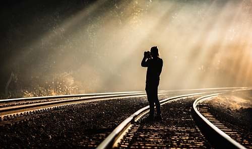 person person holding camera standing on train track while taking photo nashville