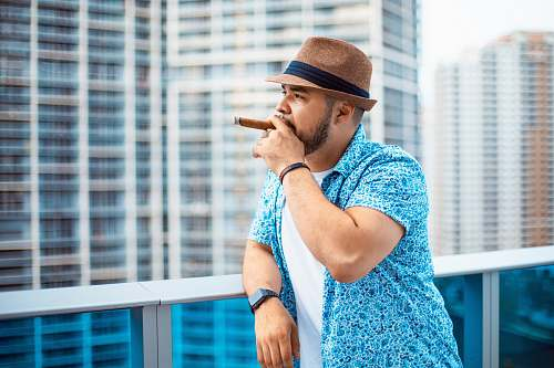 person person leaning against white metal railing while smoking cigar people