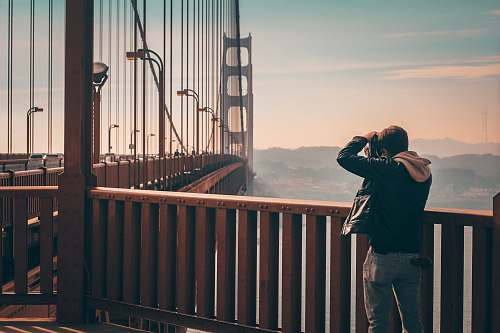 person person standing on bridge taking picture people