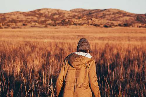 person person wearing jacket walking in brown grass field people