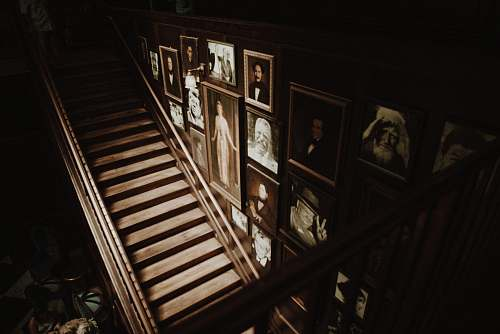 person photo frames hanged on wall beside empty brown wooden stairs people