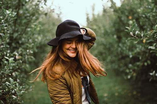 person selective focus photography of woman holding her hat while smiling people