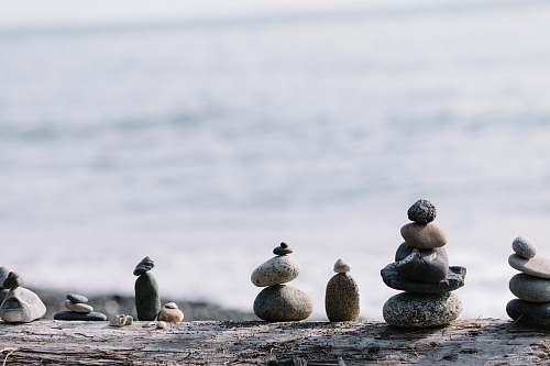 person shallow focus photo of balance stones pebble