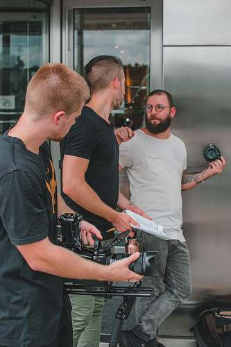 person three men holding cameras beside grey building people