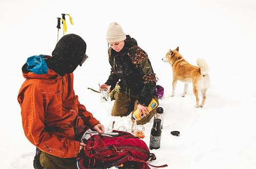 person two persons sitting on snowy ground apparel