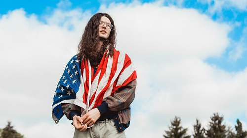 person U.S. America flag on man wearing brown jacket people