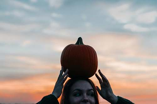 person woman carrying pumpkin on head people