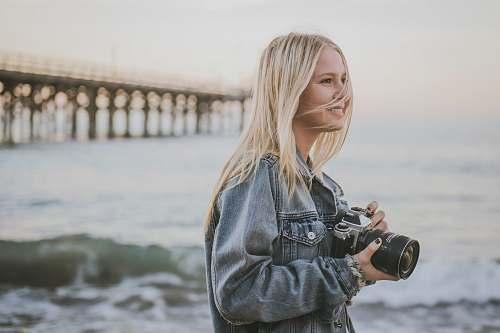 person woman holding camera standing on seashore camera