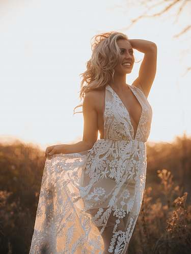 photo people woman holding her dress and head near grass during golden hour person free for commercial use images