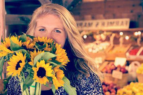 people woman in blue and white floral top holding sunflower buoquet person