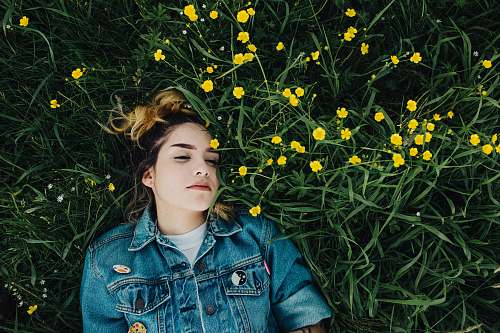 people woman in blue chambray jacket lying on green grass person