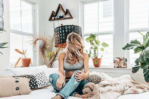 person woman in gray sports bra sitting on bed near windows cushion
