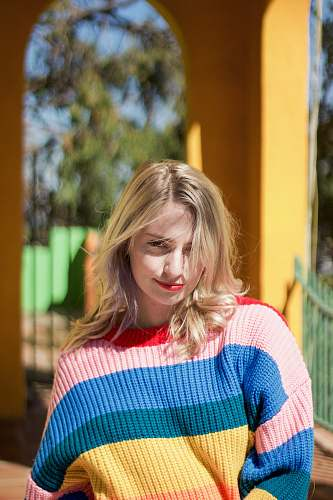 apparel woman in red, pink, blue, and yellow striped knit sweater clothing