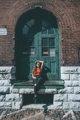 people woman sitting in front of green wooden door person