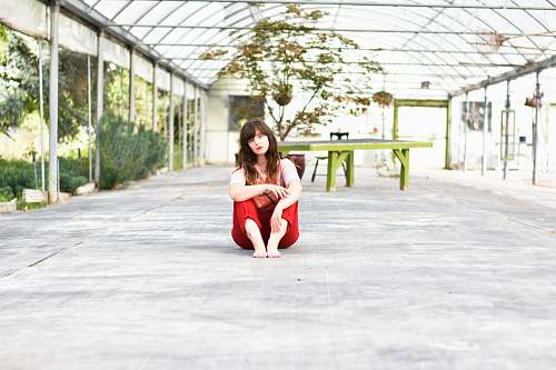 person woman sitting on gray concrete surface posing for photo people
