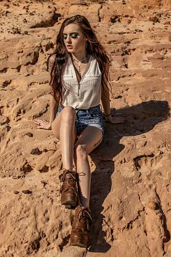 apparel woman sitting on rock during daytime clothing