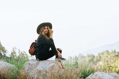 people woman sitting on rock in forest person