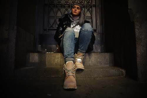 person woman sitting on top of gray concrete stair near door people