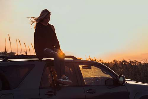 people woman sitting on vehicle roof taken during golden hour person