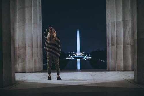 person woman standing inside building facing tower landmark people