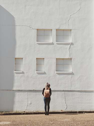 person woman standing on front of white building photographer