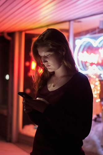 person woman using smartphone in front of red and blue lighted glass store people