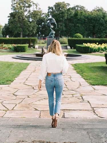 denim woman walking near black water fountain jeans