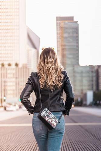 person woman wearing black leather jacket and blue denim bottoms standing on gray concrete surface near buildings during daytime people