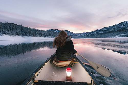 boat woman wearing black winter jacket sitting on boat paddling toward mountains canoe