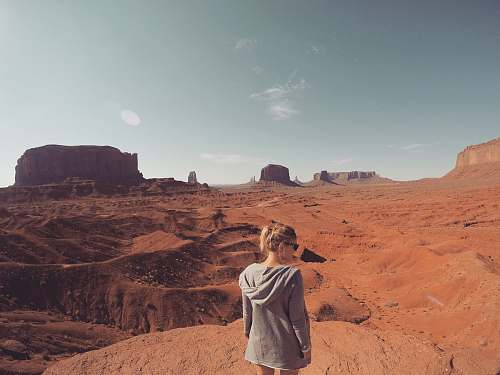 people woman wearing gray hooding looking at Monument Valley at daytime desert