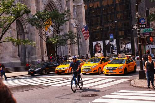 person yellow taxi cab on the street during daytime asphalt