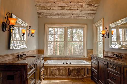 home comfort room with white bathtub and brown wooden cabinets bathroom