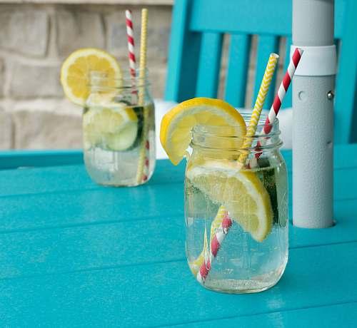 drink sliced lemon in clear glass jar alcohol